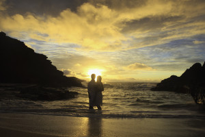 young mixed newlywed couple at sunrise on Eternity Beach
